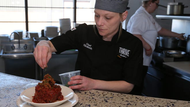 Chef Elizabeth Hinner garnishes smoked meat loaf that is covered in a sweet-corn barbecue sauce and topped with crispy onions at Thrive Foodery in Wausau, Friday, March 6, 2015.