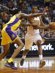 T.J. Warren (right) drives the lane against the Lakers' Brandon Ingram during the first half of Monday's loss.