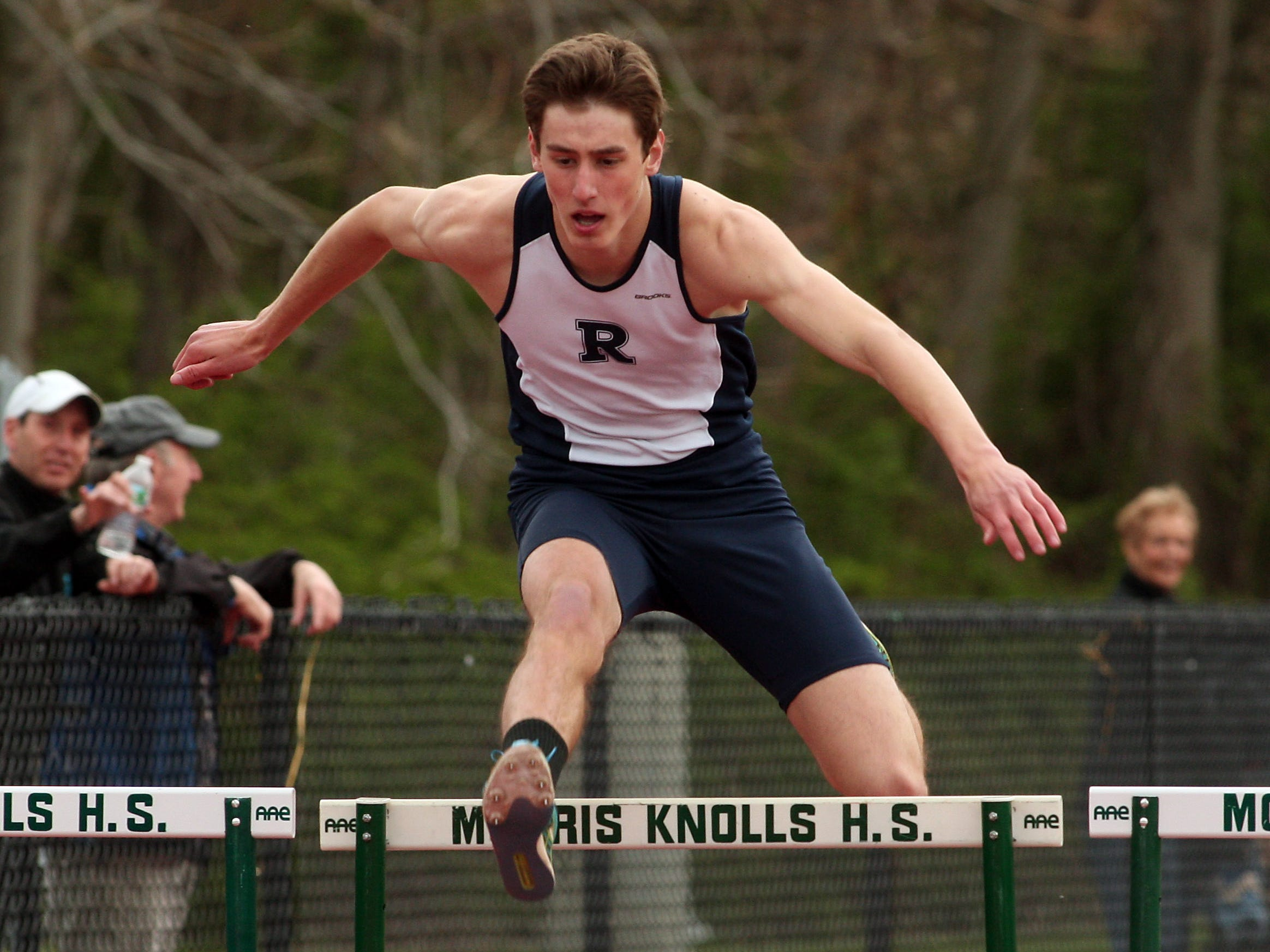 Randolph senior Greg Stickle clears the final hurdle on the first day of the Morris County Relays.