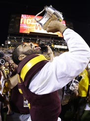 ASU quarterback Manny Wilkins celebrates with the Territorial Cup after beating the Wildcats last November in Tempe.