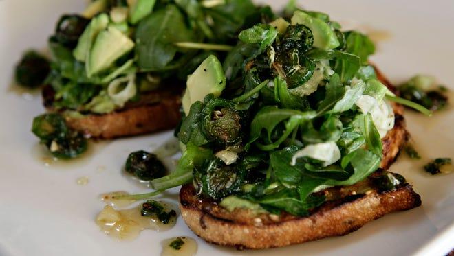 Whole-wheat toast is topped with fresh greens, avocado smear and a Serrano-garlic glaze.