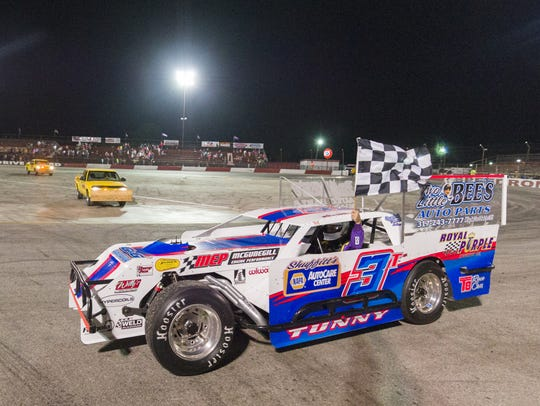 Mark Tunny takes a parade lap with the checkered flag