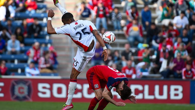 New England Revolution defender Darrius Barnes and Chicago Fire forward Mike Magee collide during the second half at Toyota Park.