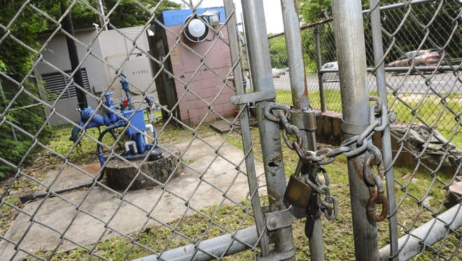 In this August 2016 file photo, a locked gate restricts access to a Guam Waterworks Authority water well located in Hagåtña, as motorists drive pass along Route 4 near McDonald's.