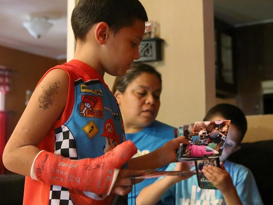 Seven-year-old Zayden Melendez shows photographs of his mother at his grandmother's home on Sept. 7.