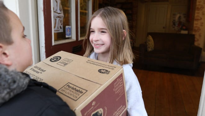 Audrey Nelson, 8, of Penfield sold 757 boxes of Girl Scout cookies.  They had just received their order of cookies and her family was helping bring the boxes of cookies in.  Passing her a case was her brother, Harper.