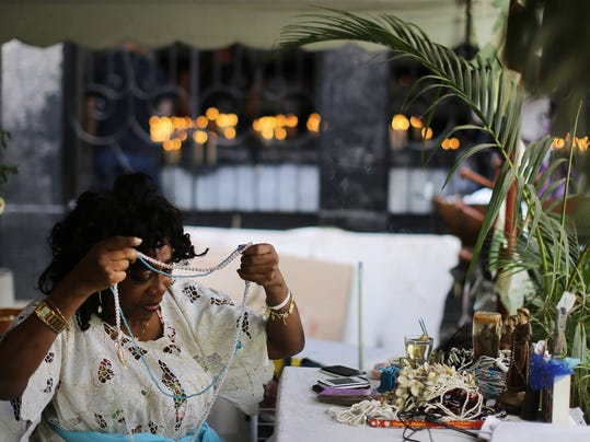 """Rita de Cassia Marciano, who is a """"mae de santa,"""" or practitioner of the syncretic Afro-Brazilian religion Candomble, prepares to attend clients in downtown Rio de Janeiro, Brazil, Thursday, June 26, 2014. Unlike her compatriots, Rita de Cassia Marciano doesn't get too stressed out during Brazil's World Cup matches. She knows Brazil is going to win its sixth title: The gods told her so. (AP Photo/Leo Correa)"""
