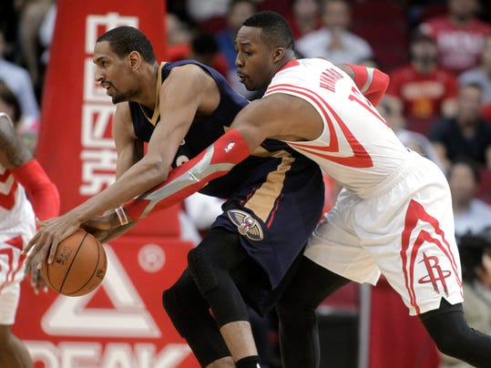 Houston Rockets center Dwight Howard defends New Orleans Pelicans Alexis Ajinca during the first quarter of an NBA basketball game, Saturday, April 12, 2014, in Houston. (AP Photo/Patric Schneider)