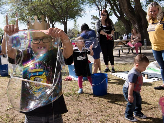 Cuauhtémoc enjoying himself making huge bubbles at the Springfest event held at Young Park.