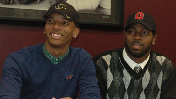 Dwayne Stanford (left) and Adolphus Washington proudly display Oregon and Ohio State caps respectively on National Signing Day in 2012