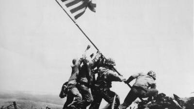 The Marines raise the American Flag on Iwo Jima.