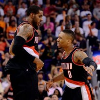 Mar 27, 2015; Phoenix, AZ, USA; Portland Trail Blazers forward LaMarcus Aldridge (12) celebrates with guard Damian Lillard (0) after making a basket against the Phoenix Suns during the second half at US Airways Center. The Trail Blazers won the game 87-81. Mandatory Credit: Joe Camporeale-USA TODAY Sports