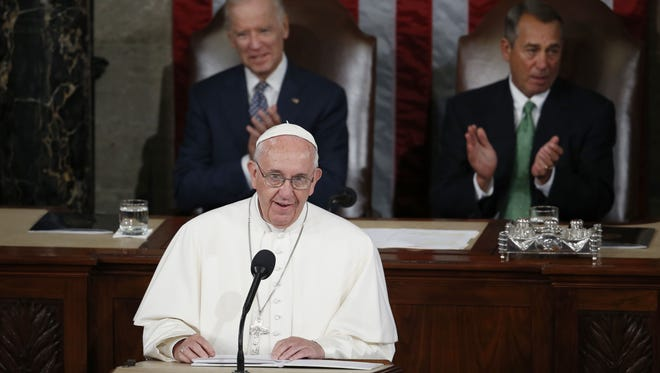 Pope Francis addresses a joint meeting of Congress on Capitol Hill in Washington, Thursday, Sept. 24, 2015, making history as the first pontiff to do so. Listening behind the pope are Vice President Joe Biden and House Speaker John Boehner of Ohio.