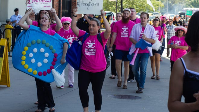 Planned Parenthood protesters follow Republican Presidential hopeful Carly Fiorina as she attends the Iowa Hawkeyes tailgate before their game in against North Texas on Saturday, September 26, 2015.
