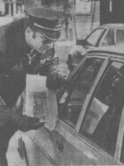 Binghamton Police Sgt. James Lewis shows Cheri Lindsey's photo to a passing motorist on Chenango Street during search efforts March 27, 1984.