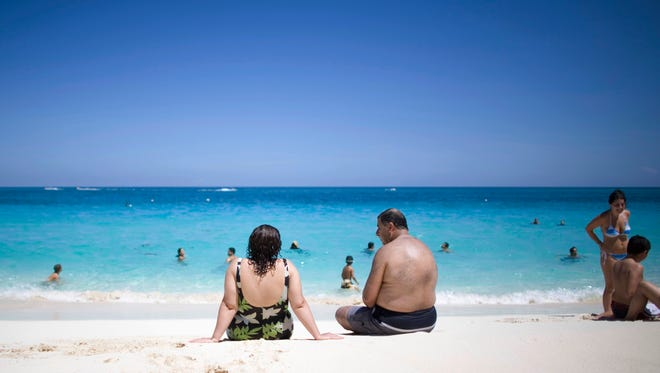 Tourists sunbathe along the beach in the Bahamas. The island vacation destination has proved popular with Greater Cincinnati travelers.