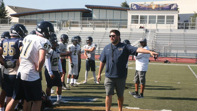 Second-year head coach Brad Mendes gives his team some instruction before running through their next set of plays.