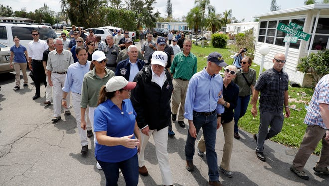 President Donald Trump, center, tours a neighborhood impacted by Hurricane Irma, Thursday, Sept. 14, 2017, in Naples, Fla.  Walking to the right of the President is Florida Gov. Rick Scott.  Behind the President is Sen. Marco Rubio, R-Fla., first lady Melania Trump and Vice President Mike Pence.   (AP Photo/Evan Vucci)