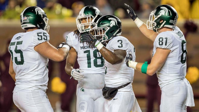Michigan State Spartans running back LJ Scott (3) celebrates with offensive tackle Jordan Reid (55), wide receiver Felton Davis III (18) and tight end Matt Sokol (81) after scoring a touchdown in the first half against the Minnesota Golden Gophers at TCF Bank Stadium.