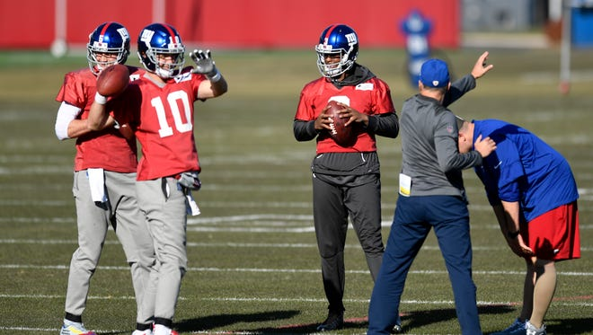 New York Giants quarterback Geno Smith stretches with Eli Manning (10) and Davis Webb, far right, during NFL football practice on Wednesday, November 29, 2017 in East Rutherford, NJ.