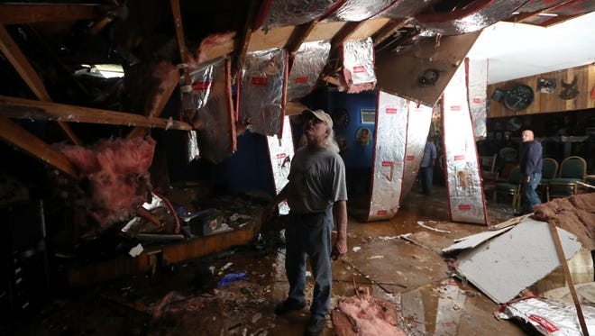 """Gary Anton, who runs the the Bradfordville Blues Club with his wife Kim, surveys the damage to his establishment after a 250-year-old oak tree came crashing down through the roof on Tuesday. """"When I first came in my heart sunk, It was devastating,"""" said Anton."""