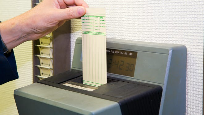 A worker is punching his time card with the automatic clock.