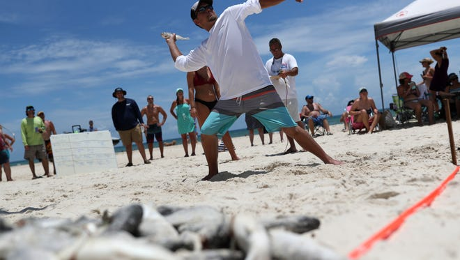 Daniel Linebaugh, of Jamestown, Ohio rears back to build up the momentum to fling a sandy fish out into the blue sky at the 27th Annual Mullet Toss sponsored by the Blue Parrot in St. George Island, Fla. on Saturday, June 9, 2018.