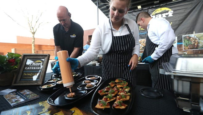 Jayda Gonzalez garnishes crab cakes at the Wharf Casual Seafood booth during the Demo Awards at the Centre of Tallahassee, a readers' choice competition for local businesses with food, drinks and a variety of displays on Thursday, June 14, 2018.
