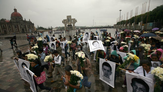 Mothers and relatives of the 43 missing students from the Isidro Burgos rural teachers college, with posters with the images of their missing loved ones walk in to attend a mass at the Basilica of Guadalupe in Mexico City, Sunday, Oct. 19, 2014. Investigators determined that 28 sets of human remains recovered from a mass grave discovered last weekend outside Iguala, in Guerrero state, were not those of any of the youths who haven't been seen since being confronted by police in that city Sept. 26.