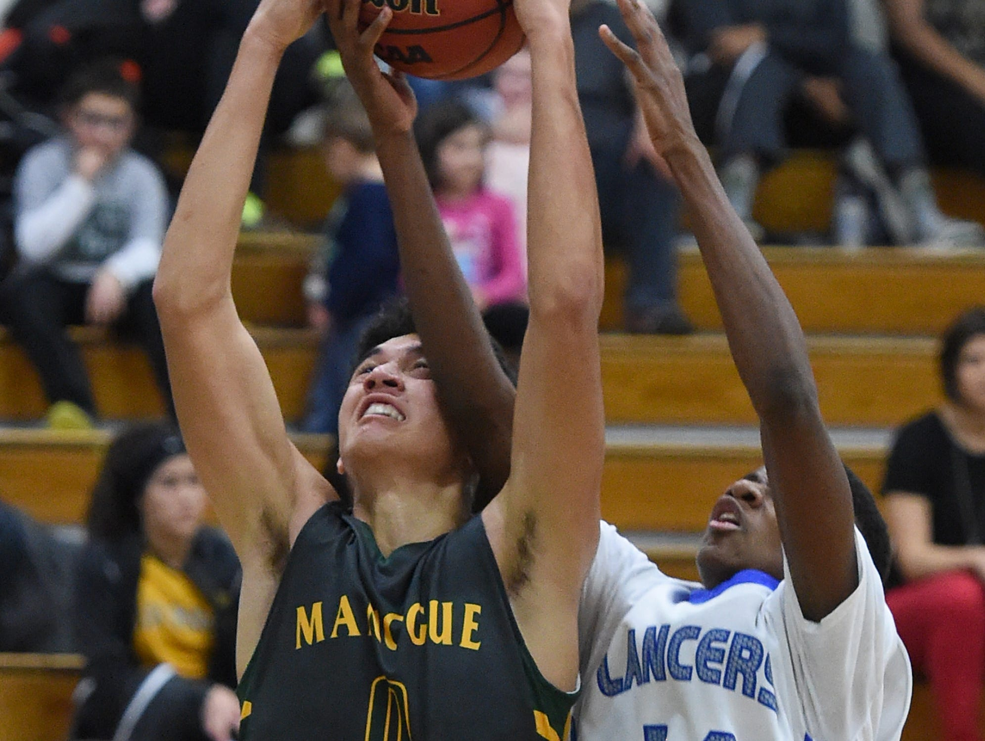 Bishop Manogue's Brevon Bansuelo and McQueen's Orlando Easter battle for the rebound in the first half of Tuesday's game at McQueen.