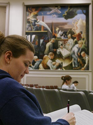 A student is shown in 2002, doing work near a controversial 12-foot mural in Woodburn Hall Room 100 a heavily-used lecture hall. The 1930s artwork by Thomas Hart Benton depicts a Ku Klux Klan rally with a burning cross.
