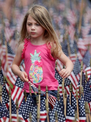 Caroline Speicher was one of the hundreds of volunteers that placed 15,000 flags on the Great Lawn at Waterfront Park. The flags honor police, corrections, sheriffs, EMT, firefighters, federal agents and veterans.