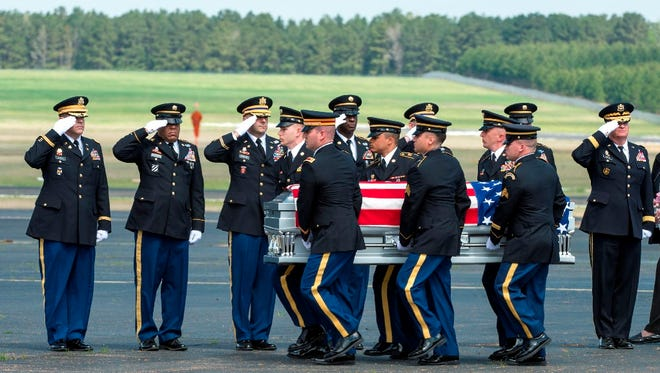 Maj. Gen. Glenn H. Curtis, adjutant general of the Louisiana National Guard, and other senior leaders honor fallen Army Chief Warrant Officer 4 David Strother during a deplaning ceremony at Esler Field on Tuesday. Strother was killed along with three other guardsmen and seven Marines in a Black Hawk crash in Florida.