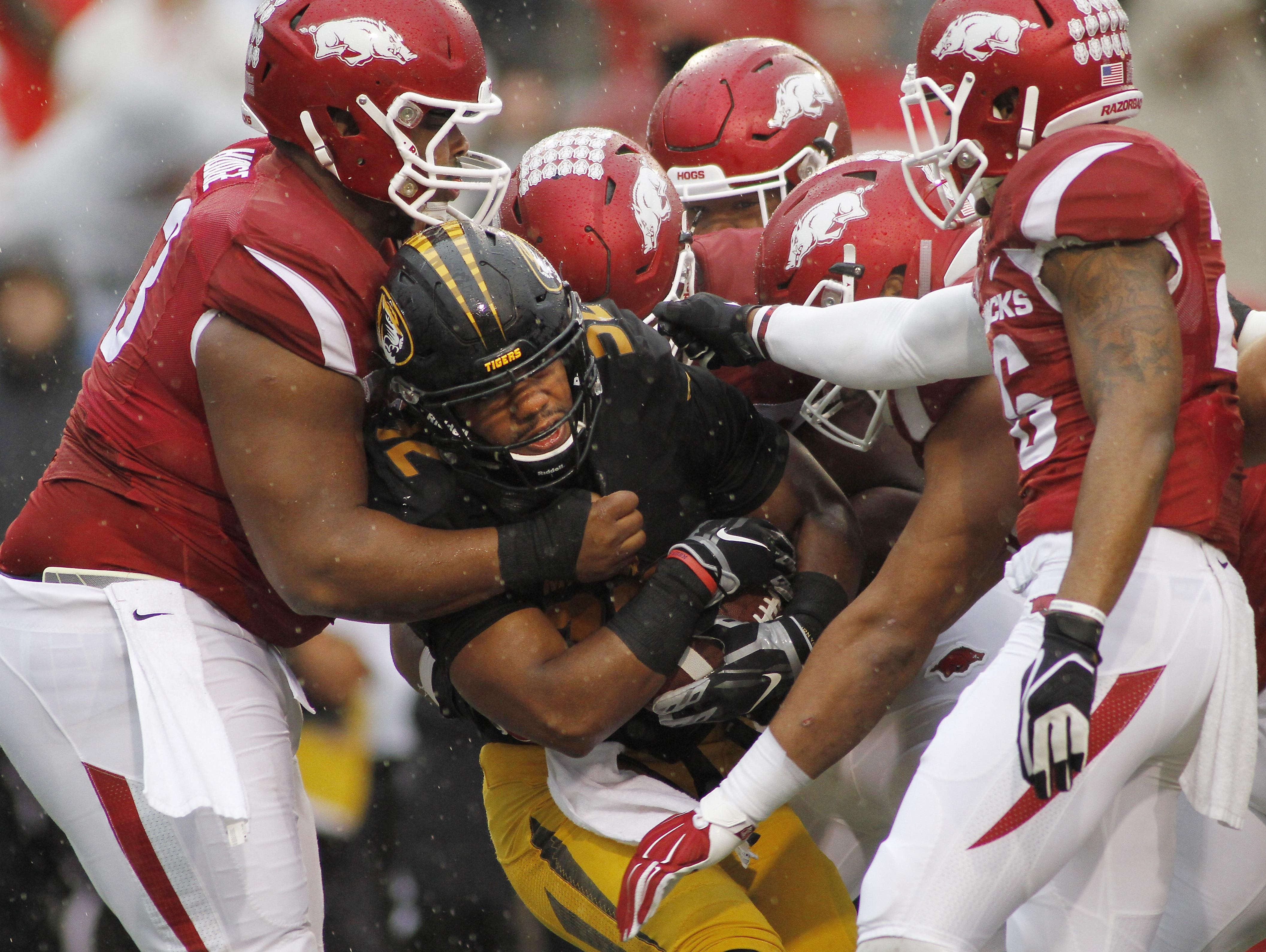 Arkansas' defense collectively takes down Missouri's Russell Hansbrough (32) during the first half on Friday in Fayetteville.