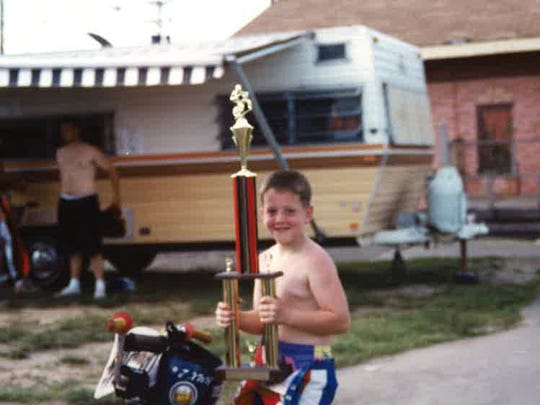 Shane O'Neill as a child, holding a trophy he earned as a BMX racer.