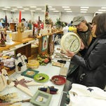 Jerry and Kathy Zychowski of Menomonee Falls look at a wall clock at one of the booths in the Action Reporter Media Ultimate Indoor Garage Sale at the Fond du Lac County Fairgrounds in 2013. Booths are still available for this year's event on March 7.