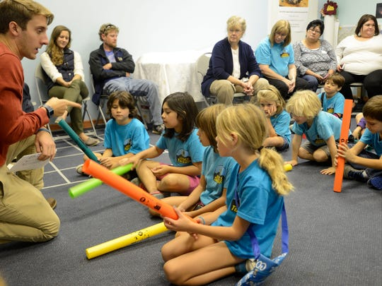 "Educational Intern Cory Vanauken teaches students from the Mountain Discovery Charter School in Bryson City how to use Boomwackers to play ""Twinkle Twinkle Little Star"" at The Colburn Earth Science Museum where they learned about sound on Wednesday, September 30, 2015."