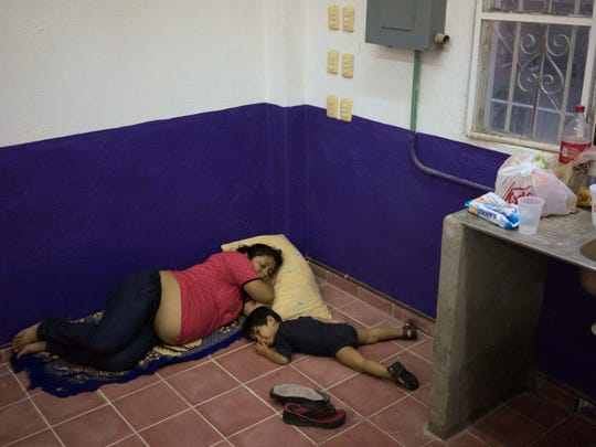 A pregnant woman and her child rest inside a shelter