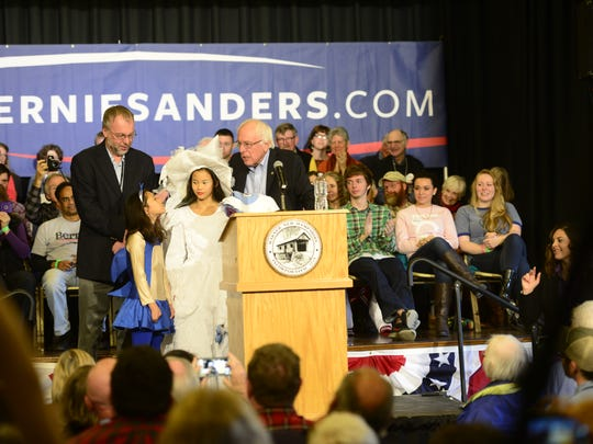 Bernie Sanders welcomes three grandchildren to the stage wearing Halloween costumes at a campaign event in Warner, New Hampshire on Saturday.