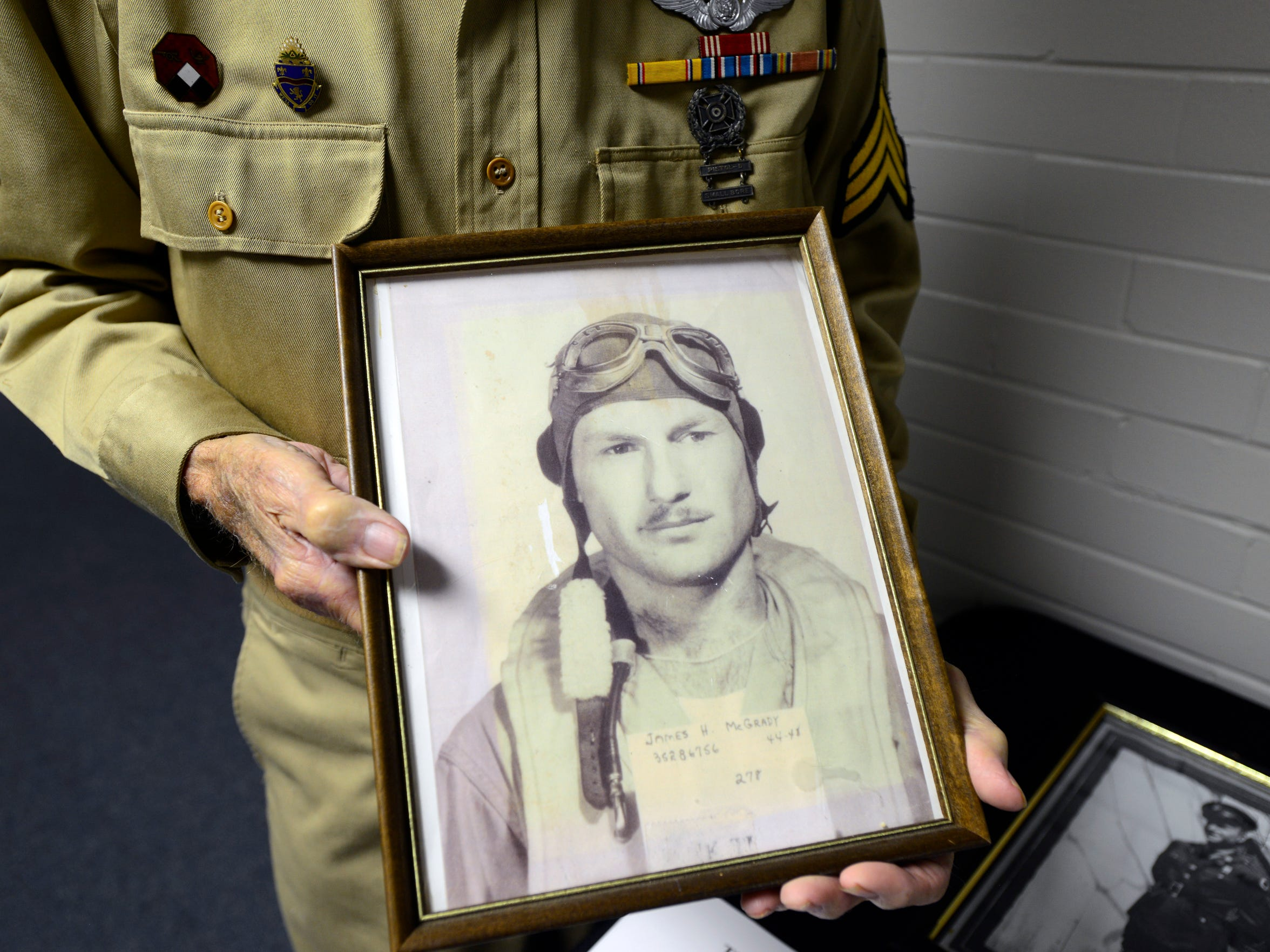 World War II veteran Jim McGrady, 97, of Fremont,  holds a picture of himself from 1944 when he flew a B-24 Bomber.
