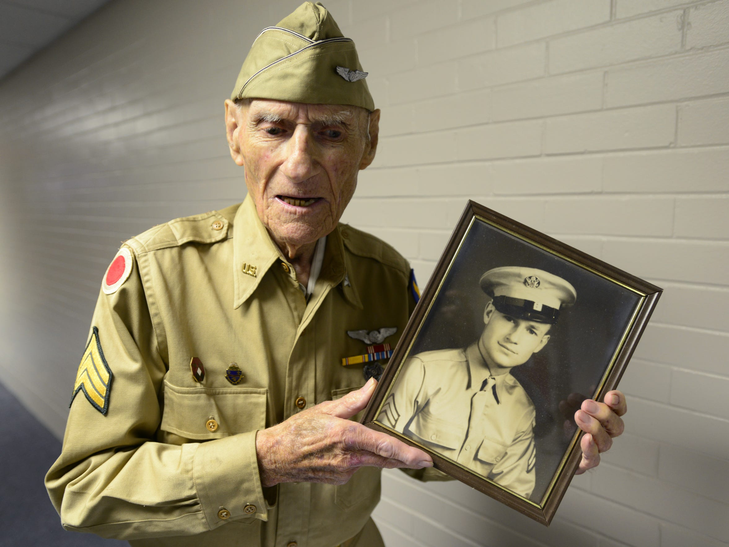 Jim McGrady, 97, of Fremont, holds a picture of himself from 1942 when he served in field artillery.