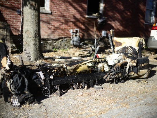 A charred, soggy couch smolders in the driveway of