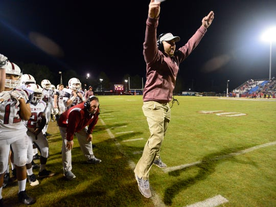 Tate High School head coach Jay Lindsey celebrates a touchdown last season while taking on Pine Forest in the Region 1-6A final. Tate beat Pine Forest 31-7.