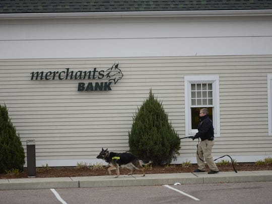 A canine police unit searches the area for a bank robbery suspect in South Burlington.