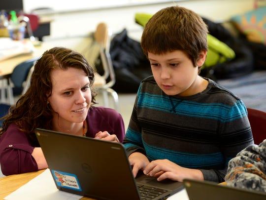 Fourth grade teacher Kaitlin Frando helps Gilbert Simms, 10, as he works on a Chromebook recently at West Pensacola Elementary School.