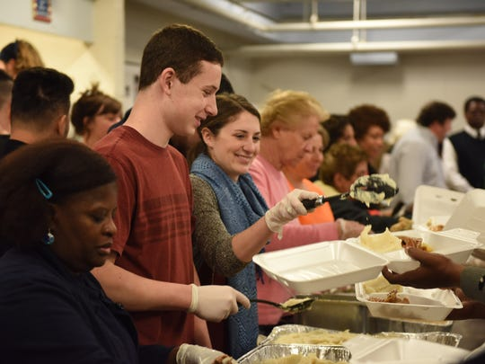 Caitlin Dempsey (center) serves scoops of mashed potatoes to hungry diners at the 32nd Annual Hickey Thanksgiving Dinner at the Family Partnership Center, 29 North Hamilton St., in the City of Poughkeepsie Thursday.