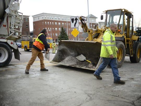 Winooski Public Works employees shovel spilled cement