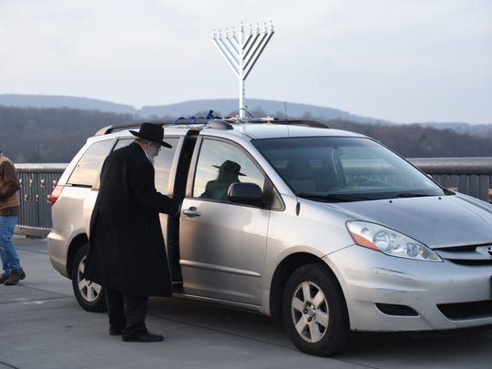 A festive Rabbi Yacov Bornstein of the Chabad of the Mid-Hudson Valley showed up to a menorah lighting on the Walkway Over the Hudson Sunday with a menorah strapped to his minivan.