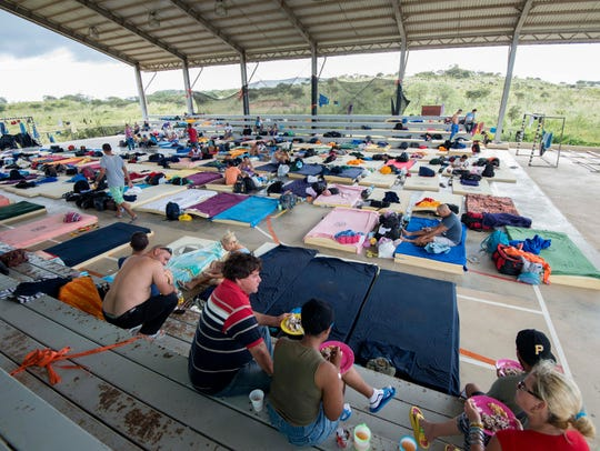 Members of a group of 300 Cuban migrants rest in a