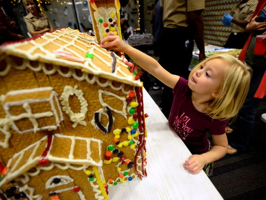 Willow Cooke, 4, helps decorate a gingerbread house